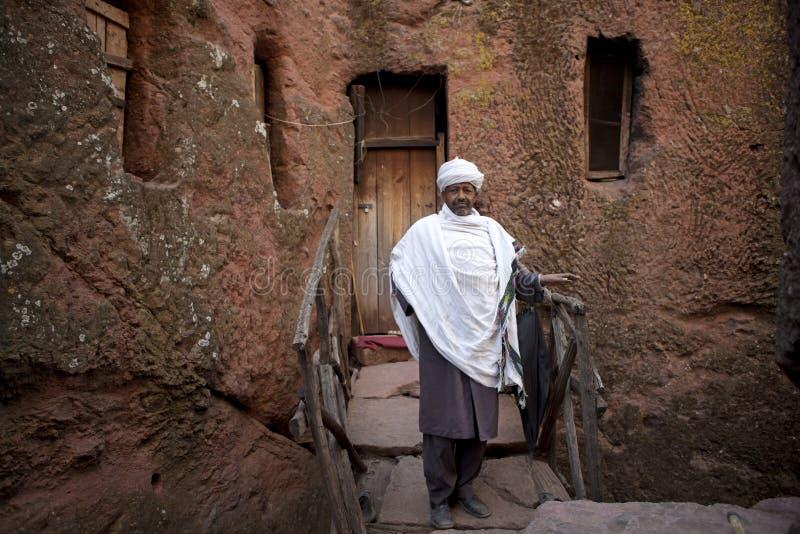 A man outside a monolithic church, Ethiopia stock photos