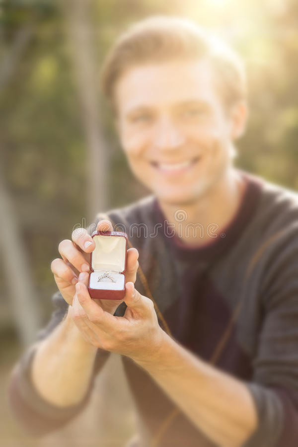 Man outside proposing. Man kneeling outside proposing with diamond ring royalty free stock photos