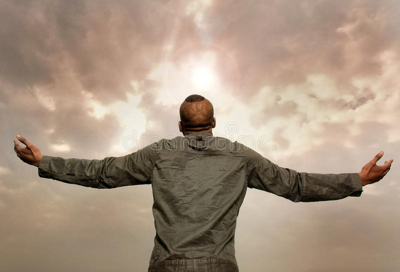 Man with outstretched arms looking at the sky stock photography