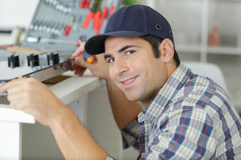 Man in overall installing kitchen royalty free stock photography