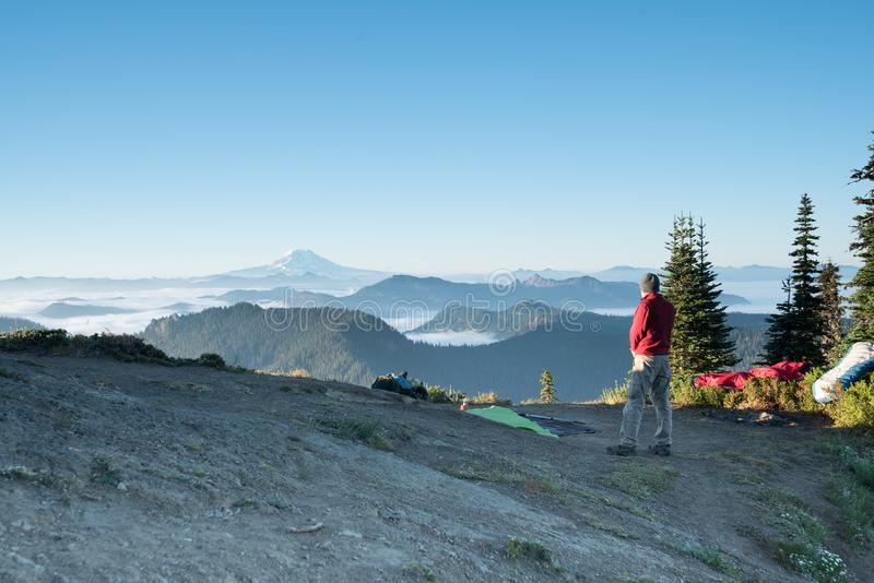 A man overlooking the mountains at his campsite with camping gear. At sunrise royalty free stock photography