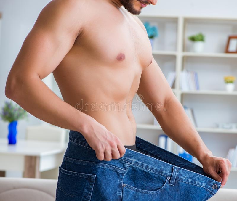 Man in oversized pants in weight loss concept stock photos
