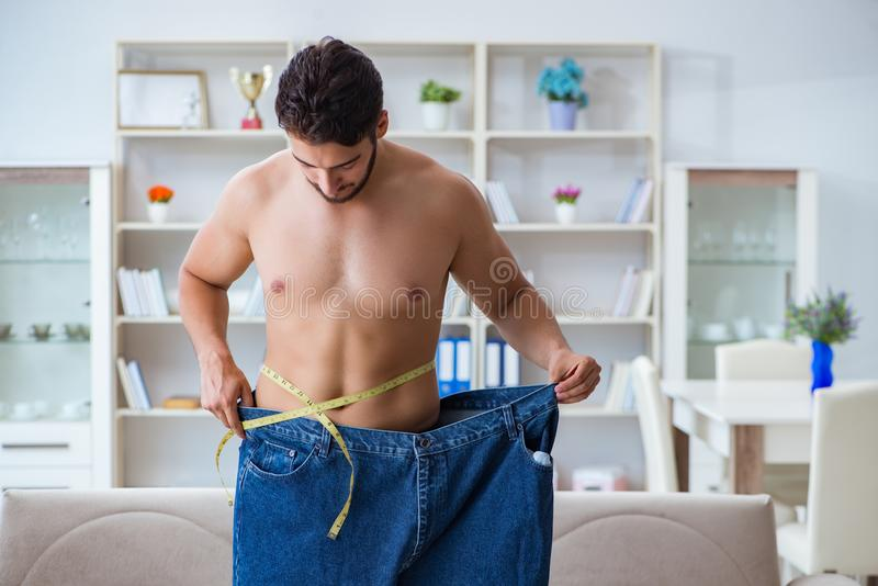 The man in oversized pants in weight loss concept stock image