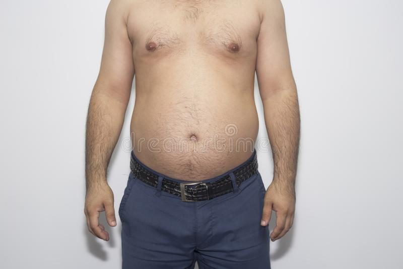 Man with overweight. symbol of beer belly, unsuccessful dieting and eating the wrong foods. Weight loss concept. stock photo