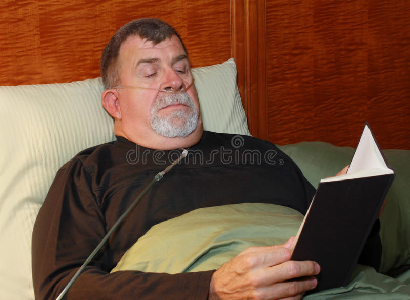 Man with Oxygen Cannula Reading in Bed royalty free stock photo