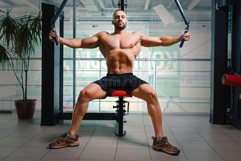 Man på armpressmaskinen Kroppsbyggare med den muskulösa torson som utarbetar på en idrottshallbakgrund Sportteknologibegrepp arkivfoton