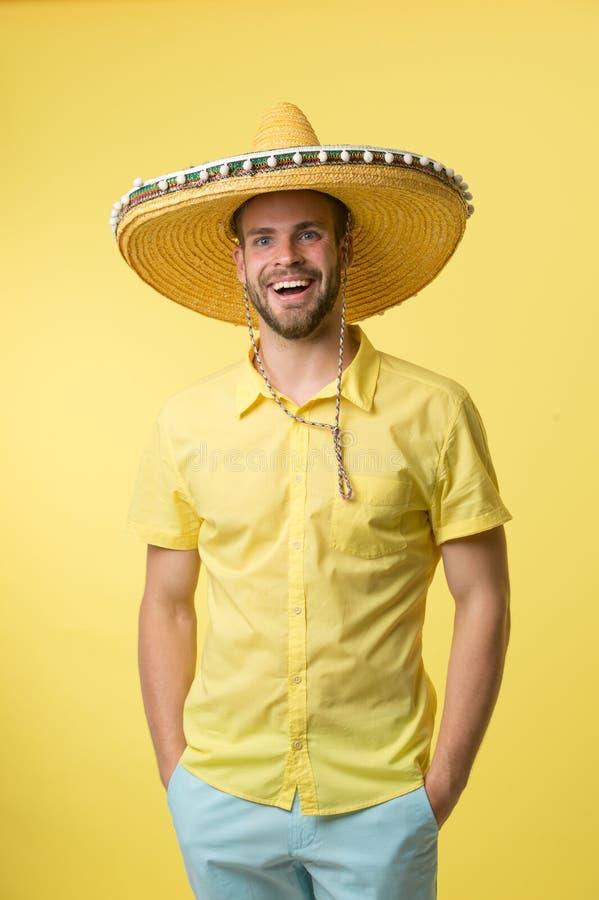 Man på att le framsidan som poserar i sombrerohatt med händer i fack, gul bakgrund Grabben med borstet ser festlig in fotografering för bildbyråer