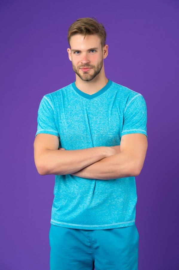 Man på att le framsidan som säkert poserar med vikta armar, violett bakgrund Grabben med borstet bär uppsättningen av sportive royaltyfri fotografi