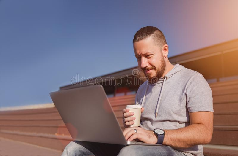 Man på bärbara datorn för bruk för kaffeavbrott royaltyfria foton