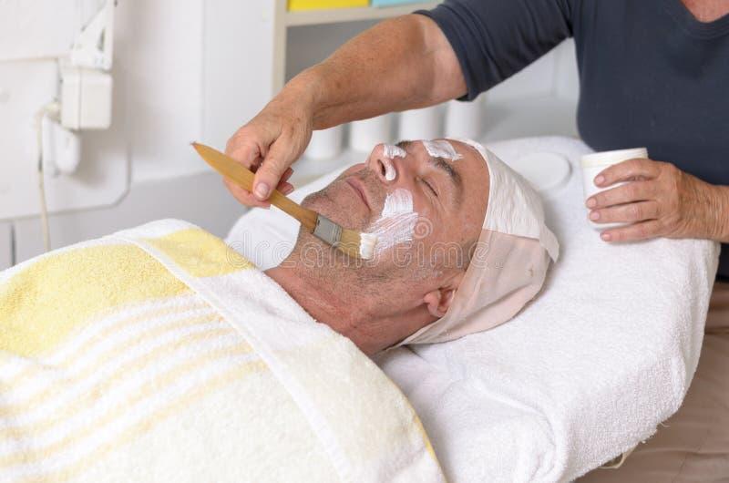 Man på behandling för ansiktsbehandling för skönhetmitthäleri royaltyfria bilder