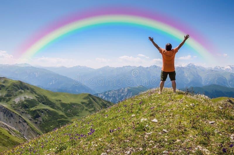Man på berget och regnbågen arkivbild