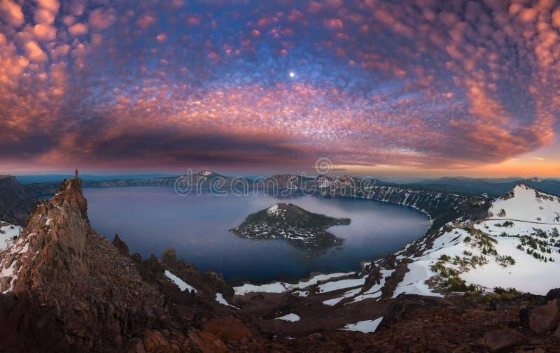 Man på bergstoppvisningkrater sjön med fullmånen royaltyfria bilder