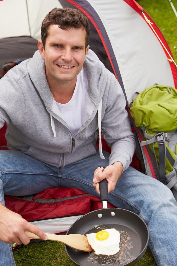 Man på campa ferie som steker ägget i panna arkivfoton