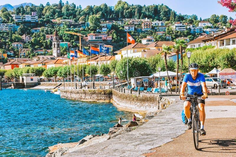Man på cykeln på promenad Ascona lyxig för turist- semesterort arkivbild