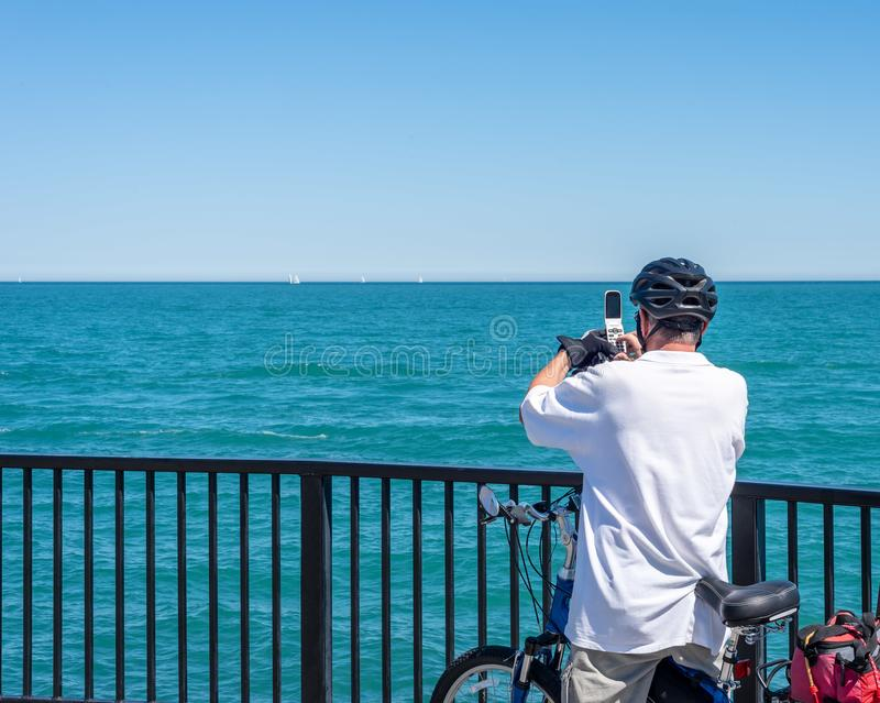 Man på cykeln som tar fotoet av Lake Michigan royaltyfria foton