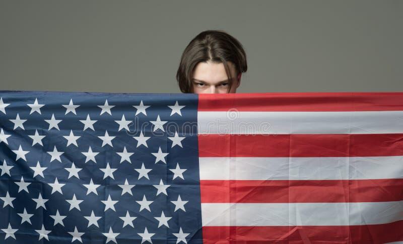 Man på den allvarliga framsidahållflaggan av USA som döljer bak flagga Grabbnederlaget i USA, Amerika skyddar honom, grå bakgrund royaltyfria bilder