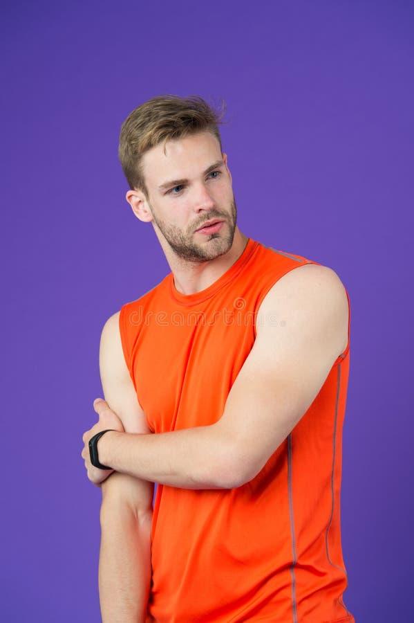 Man på den fundersamma framsidan som poserar i sportive kläder, violett bakgrund Grabben med borstet bär den sportive skjortan oc arkivbilder
