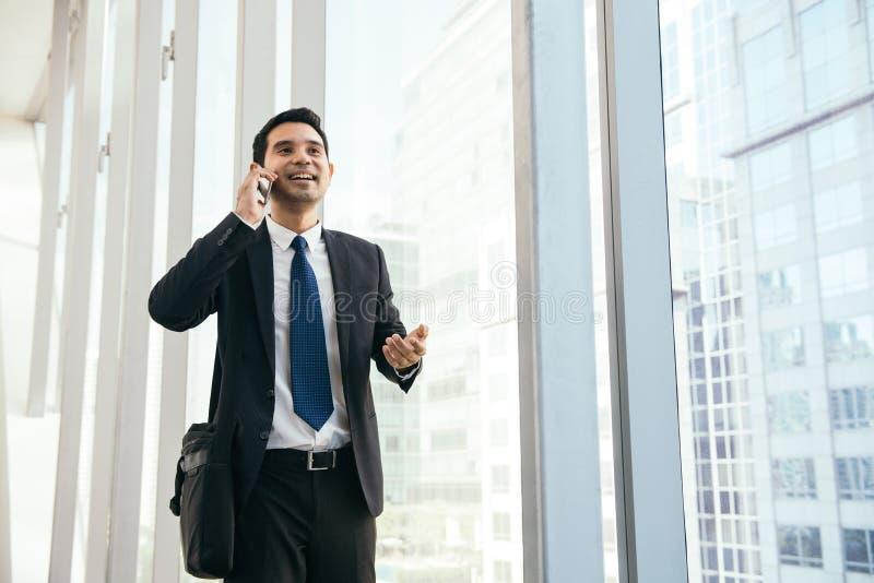 Man på den smarta telefonen - ung affärsman i flygplats Tillfällig stads- yrkesmässig affärsman som använder att le för smartphon royaltyfri bild