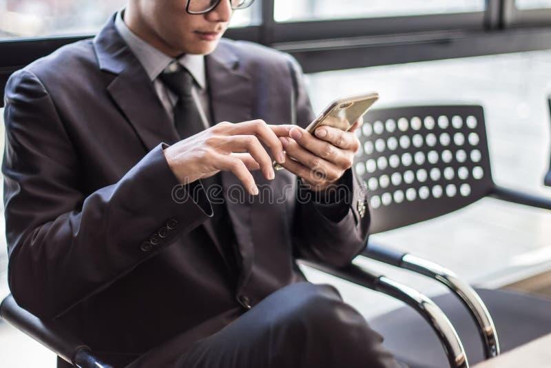 Man på den smarta telefonen - ung affärsman i flygplats Tillfälligt stads- royaltyfri foto