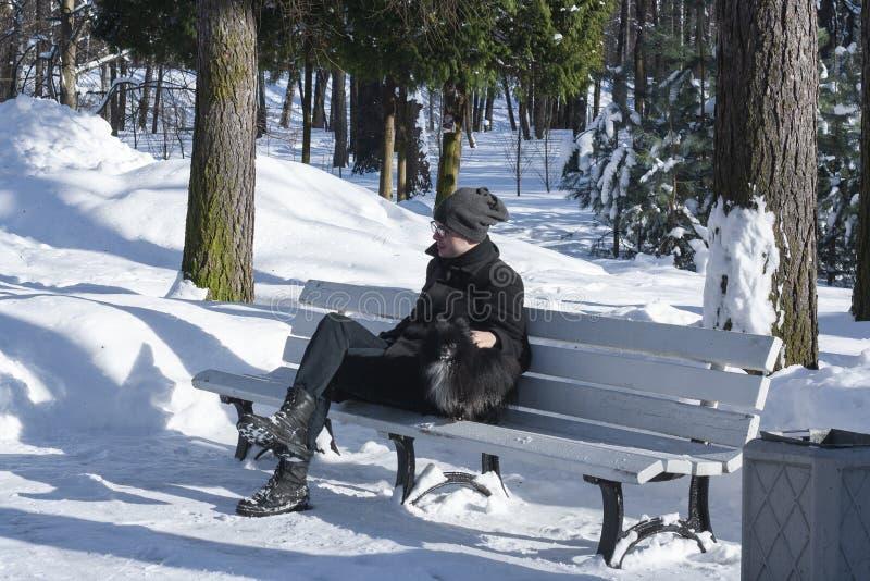 Man på en bänk i parkera Kall morgon Manvinter Man på bänken staden nära den järnväg vägen skiner snowsunen för att övervintra tr royaltyfri foto