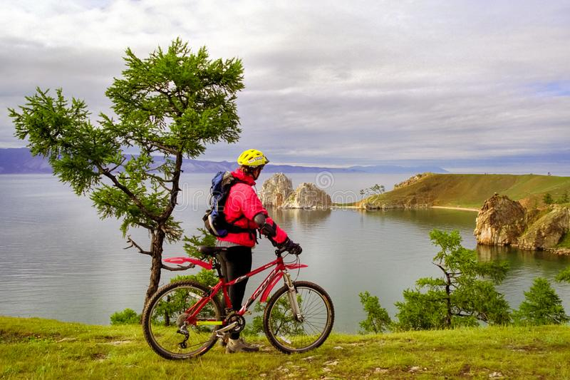 man på en cykel på kusten av Baikal royaltyfri bild