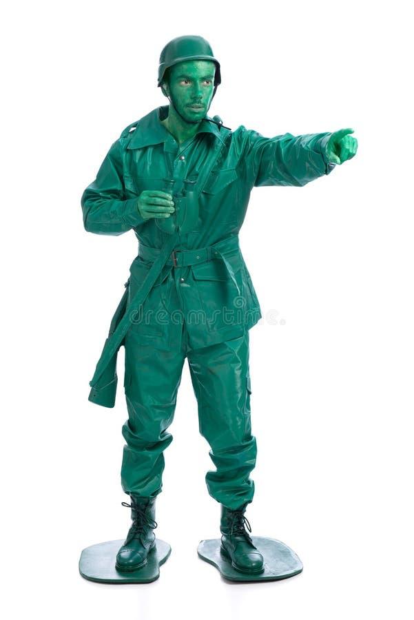 Man på en grön dräkt för leksaksoldat fotografering för bildbyråer