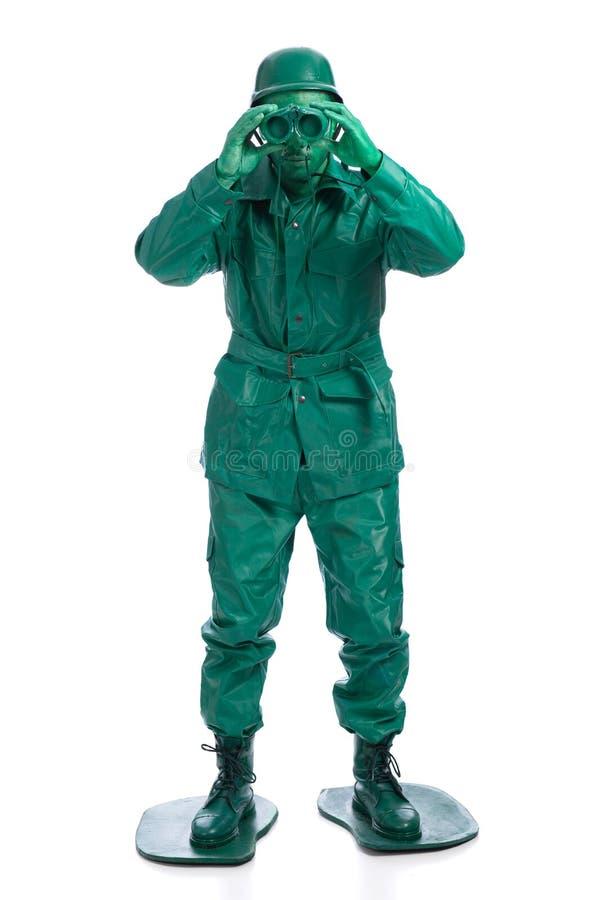 Man på en grön dräkt för leksaksoldat royaltyfri bild