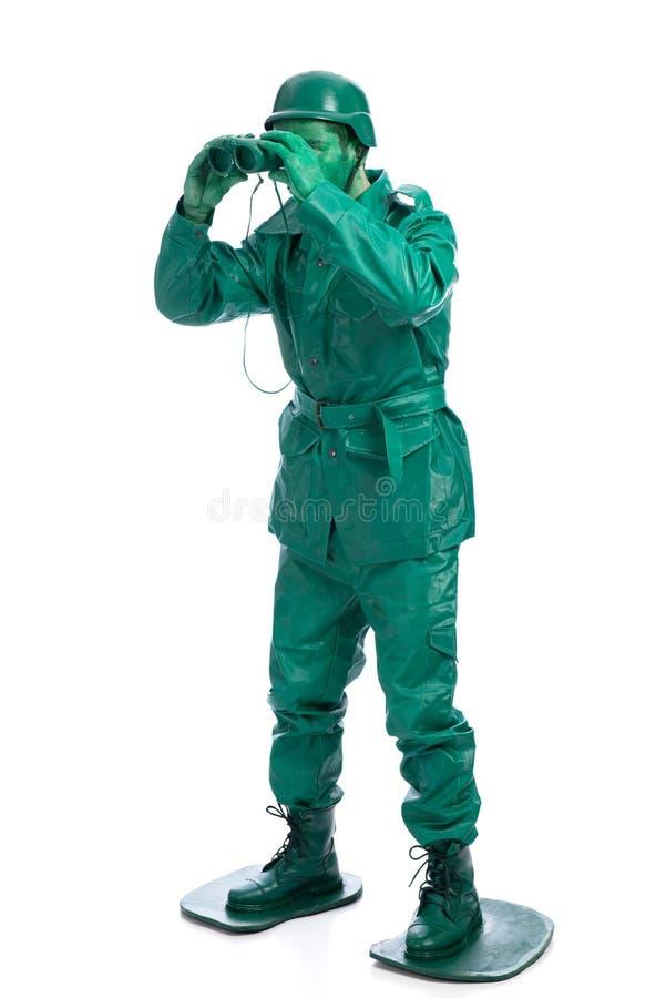 Man på en grön dräkt för leksaksoldat arkivbilder