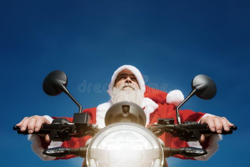 Man på en moped i en typisk Santa Claus dräkt arkivbild
