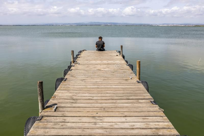 Man på en skeppsdocka vid sjön på morgonhimmel royaltyfria bilder