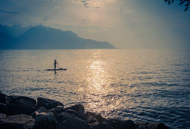 Man på en surfingbräda med skoveln på sjön Leman, Schweiz royaltyfri foto