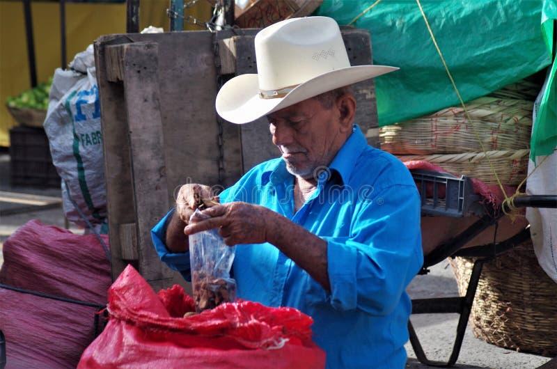 Man på en till salu tamarindfrukt för Honduras marknadsemballage arkivbilder