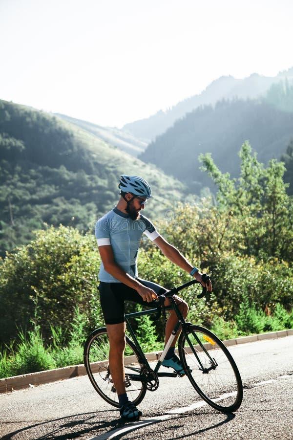 Man på en vägcykel i bergen arkivfoton