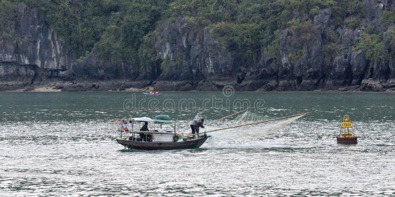 Man på fartygfartygfiske på den Halong fjärden royaltyfri bild