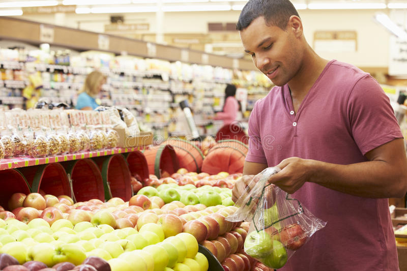 Man på frukträknaren i supermarket royaltyfri bild