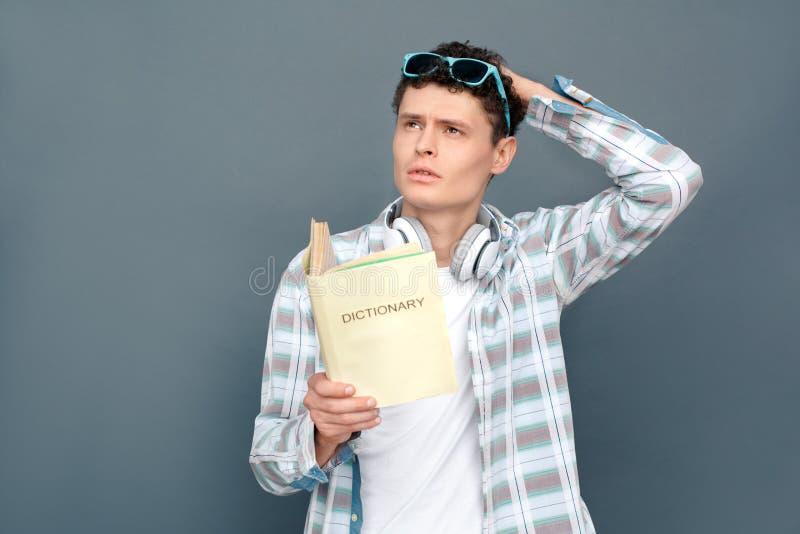 Man på grått anseende för väggturismbegrepp med ordboken som memorerar fundersamma ord arkivbilder
