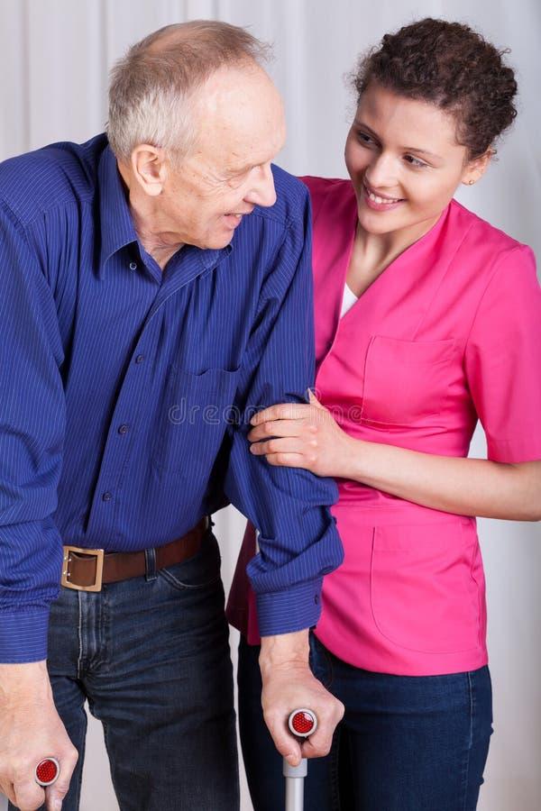 Man på kryckor och hans sjuksköterska royaltyfri foto