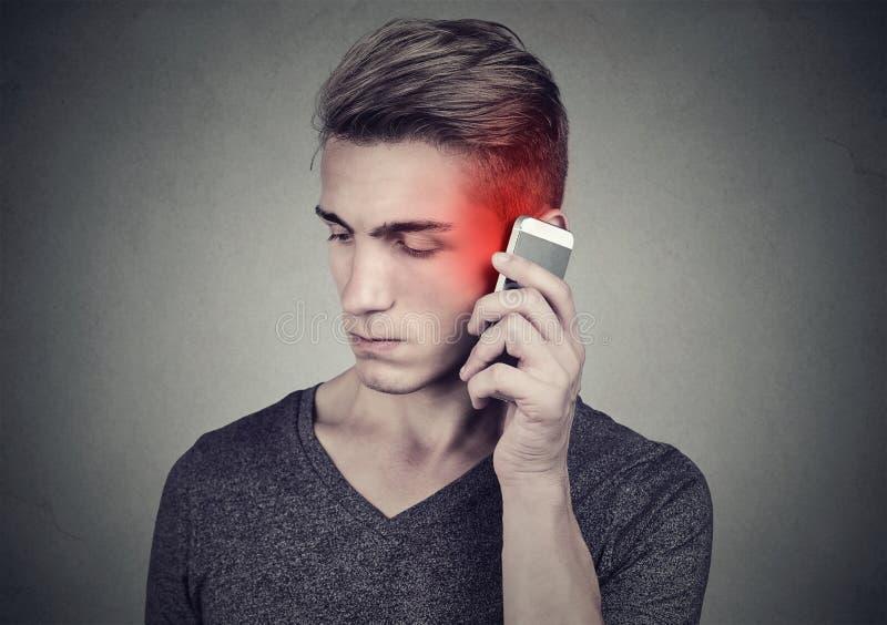 Man på mobiltelefonen med huvudvärk Uppriven olycklig grabb som talar på en telefon arkivfoton