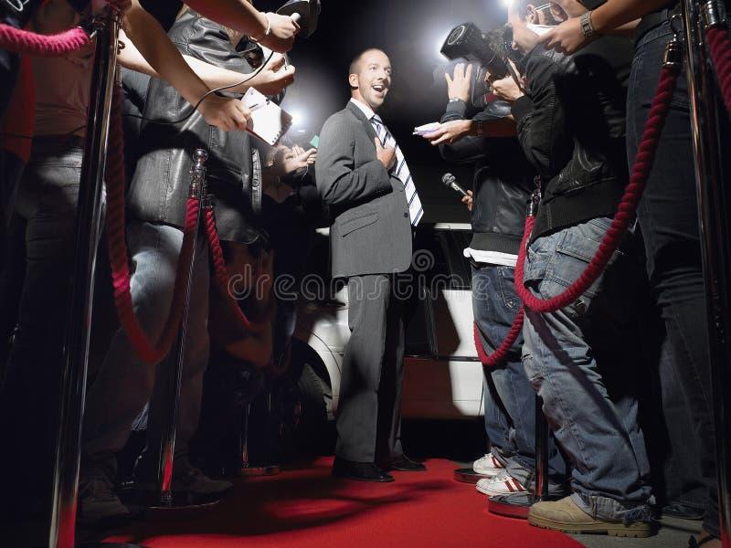 Man på röd matta som poserar i Front Of Paparazzi arkivbild