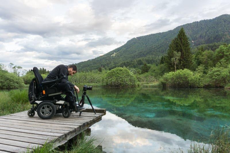 Man på rullstolen genom att använda den mirrorless kameran nära sjön i natur arkivbild