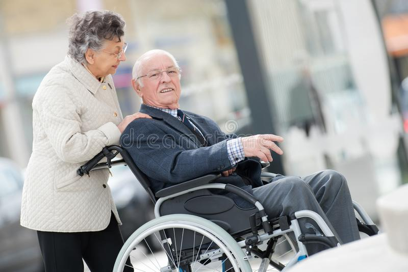 Man p? rullstolen med den optimistiska frun utomhus royaltyfri foto