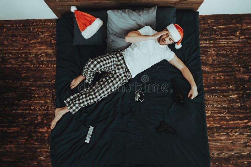 Man på säng med huvudvärk efter julparti arkivfoto