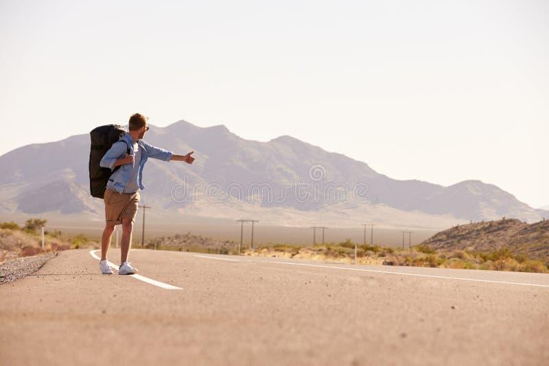 Man på semester som liftar längs landsvägen fotografering för bildbyråer