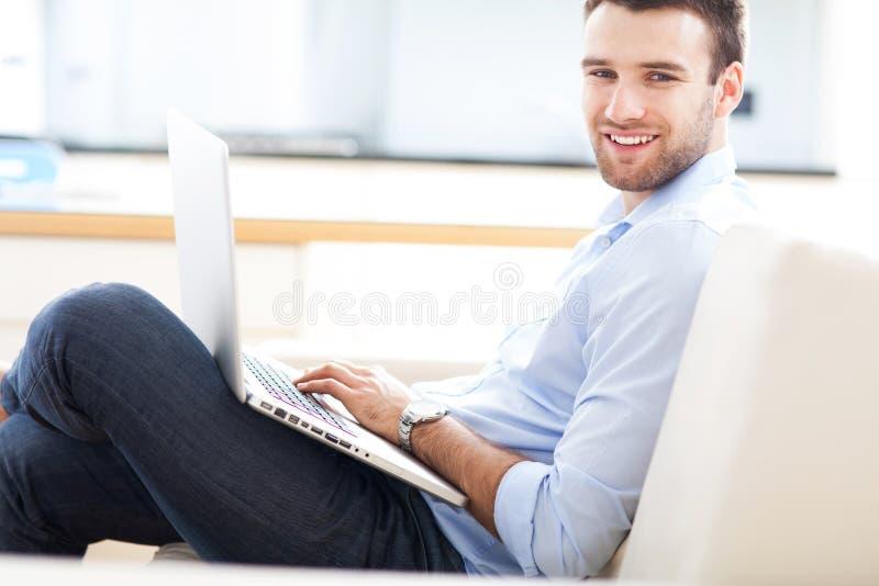 Man på soffan med bärbara datorn royaltyfria bilder