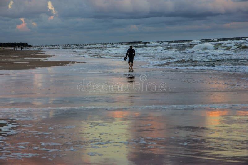 Man på stranden på solnedgången över det baltiskt royaltyfria bilder