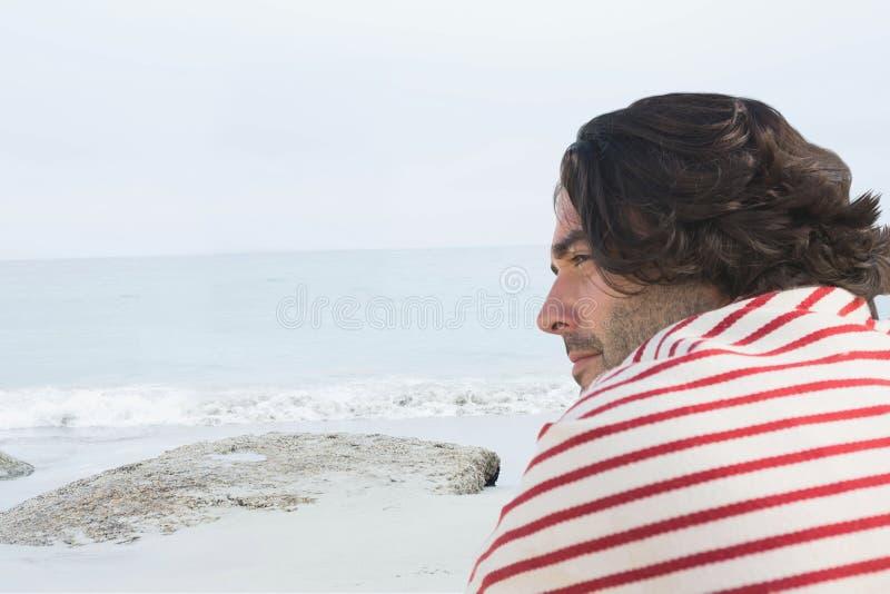 Man på stranden som ser till det vänstert fotografering för bildbyråer