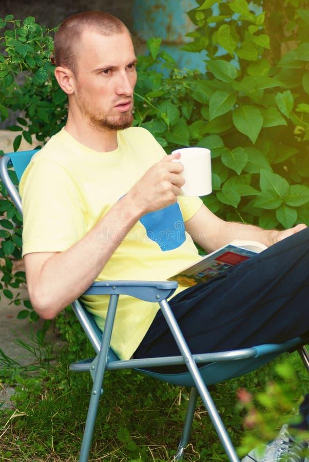 Man på trädgården som dricker kaffe och läseboken arkivfoton