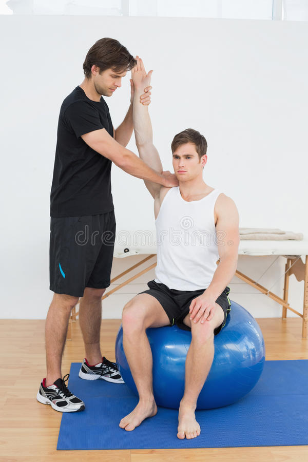 Man på yogabollen som arbetar med en fysisk terapeut royaltyfri bild