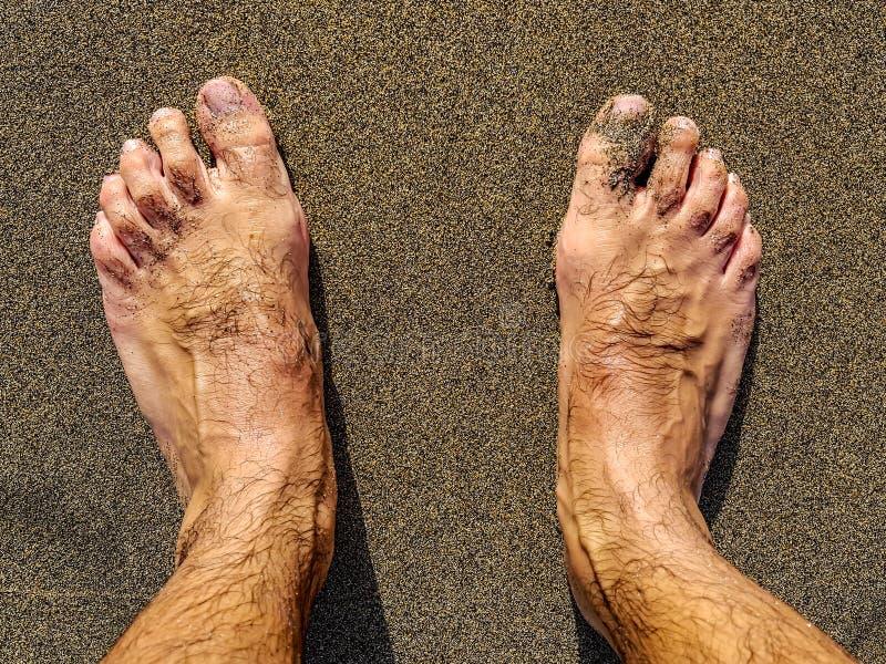 man& x27; pés e pés de s na areia preta de uma praia em Tenerife, Espanha fotos de stock royalty free