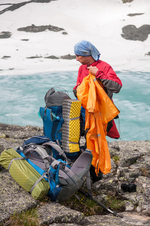 Man is packing his backpack whike hiking. In Altain mountains royalty free stock image